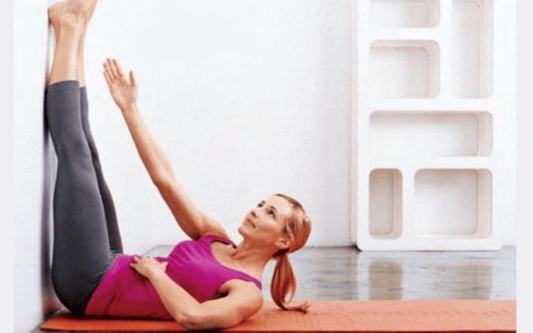 gác chân lên tường giảm mỡ bụng kết hợp với vươn tay